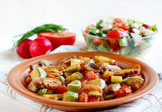 Roasted vegetables and fresh salad. Roasted vegetables on a rustic plate. Salad with fresh vegetables and  salad ingredients in the background Royalty Free Stock Image