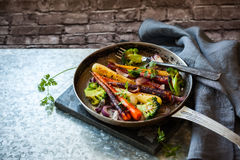 Roasted vegetables in pan. Roasted rainbow carrot and broccoli in a vintage pan, rustic style Royalty Free Stock Image