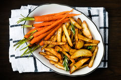 Roasted vegetables seasoned with rosemary and black pepper. Oven-baked baby carrots and potatoes in white bowl on dark table. Healthy vegetarian snack stock images