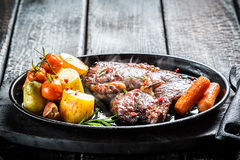 Roasted vegetables and steak with fresh herbs on barbecue dish Stock Photo