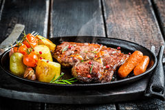 Roasted vegetables and steak with herbs on barbecue dish Stock Image