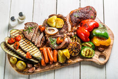 Roasted vegetables and steak with salt on wooden board Stock Photos