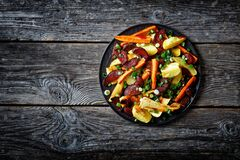 Roasted veggies on a black plate