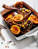 Roasted Venison Haunch with Citrus Slices. High Angle View of Roasted Venison Haunch Seasoned with Fresh Herbs and Orange Citrus Slices in Roasting Pan on White royalty free stock image