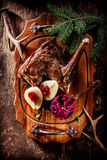 Roasted Venison Haunch with Pears on Wooden Tray. High Angle View of Roasted Venison Haunch on Wooden Tray with Prepared Pears on Rustic Table with Evergreen stock image