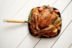 Roasted whole chicken in cast iron black pan royalty free stock images