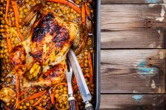 Roasted whole chicken with chickpeas, carrots and lemons Royalty Free Stock Image