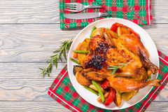 Roasted whole chicken, potatoes, baby carrots, eggplants, green Stock Photography