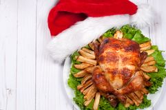 Roasted whole chicken with Santa hat. Christmas dinner. Thanksgiving table served with turkey Royalty Free Stock Image