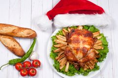 Roasted whole chicken with Santa hat. Christmas dinner. Thanksgiving table served with turkey Stock Image