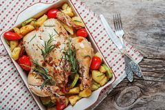 Roasted whole chicken stuffed with vegetables, tomatoes potato pepper and rosemary on vintage napkin wooden table background. With fork and knife set. Top view Stock Images