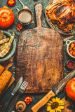 Roasted whole chicken or turkey, pumpkins, corn and harvest vegetables with kitchen knife and cutlery served around aged wooden cu Royalty Free Stock Photo
