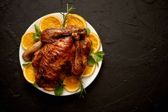 Roasted whole chicken or turkey served in white ceramic plate with oranges. And lamb`s lettuce on dark stone background. View from above stock image