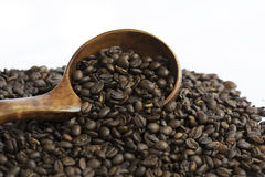 Roasted Whole Coffee Bean Selected focus. Medium roasted whole coffee bean in wooden spoon on coffee bean background Stock Photo