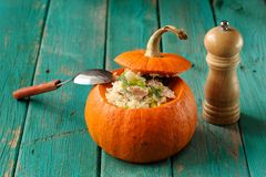 Roasted whole pumpkin with rice and meat with pepper mill. Horizontal stock photos