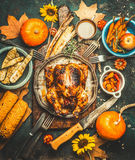 Roasted whole stuffed chicken or turkey for Thanksgiving Day , served with sauce, pumpkins, corn and autumn harvest vegetables, ki. Tchen knife and cutlery on Royalty Free Stock Photos