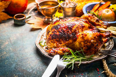 Roasted whole turkey or chicken on festive rustic table with festive autumn decoration for  Thanksgiving Day Royalty Free Stock Images