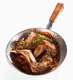 Roasted wild rabbit venison portions in a pan. Roasted wild rabbit venison portions flavored with fresh orange, zest and mushrooms served in a pan topped with royalty free stock images