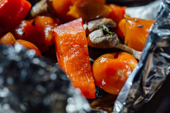 Roasted winter vegetables on aluminum foil ,Cherry tomatoes in oil, mushrooms champignons Red pepper. Healthy home made meal food Royalty Free Stock Image