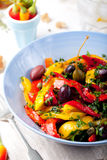 Roasted yellow and red bell pepper salad. Grilled vegetables. Roasted yellow and red bell pepper salad with capers and olives in a blue bowl on a white royalty free stock images