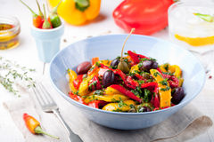 Roasted yellow and red bell pepper salad. Grilled vegetables. Roasted yellow and red bell pepper salad with capers and olives in a blue bowl on a white royalty free stock image