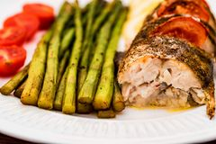 Roasted zander fillet with asparagus and lemon. Close up plate with pike perch fillet, lemon, tomato and asparagus. Healthy diet concept Stock Image