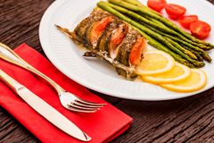 Roasted zander fillet with asparagus and lemon. Close up plate with pike perch fillet, lemon, tomato and asparagus. Healthy diet concept Stock Photo