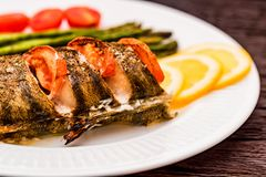 Roasted zander fillet with asparagus and lemon. Close up plate with pike perch fillet, lemon, tomato and asparagus. Healthy diet concept Royalty Free Stock Image