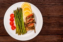 Roasted zander fillet with asparagus and lemon. Top view plate with pike perch fillet, lemon, tomato and asparagus. Healthy diet concept Stock Photo