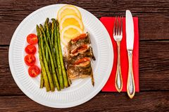 Roasted zander fillet with asparagus and lemon. Top view plate with pike perch fillet, lemon, tomato and asparagus. Healthy diet concept Royalty Free Stock Image
