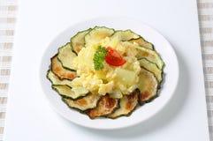 Roasted zucchini with potato egg scramble. Roasted zucchini slices with potato and egg scramble Stock Photo