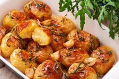 RoastedRoasted土豆用大蒜、麝香草和迷迭香在陶瓷烘烤土豆用大蒜、麝香草和迷迭香在陶瓷baki 库存图片
