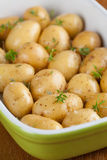 Roasting baby potatoes with thyme. Baby potatoes with thyme, olive oil and salt on baking sheet Royalty Free Stock Images