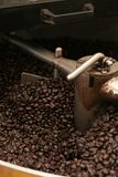 Roasting Beans. A heap of freshly roasted coffee beans sit in a roaster ready to be packaged Stock Image