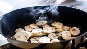 Roasting champignon mushrooms Stock Images
