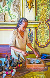 Roasting of coffee beans for Ethiopean ceremony. KIEV, UKRAINE - JUNE 4, 2017: The young Ethiopian Tigrayan woman roasts green coffee beans in a pan for Royalty Free Stock Photography