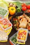 Roasting frozen vegetables and chicken food. Roasting frozen vegetables in plastic containers, roasted chicken in pan. Healthy freezer food Stock Photos