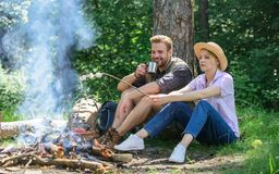 Roasting marshmallows at bonfire. Couple in love camping forest roasting marshmallows. Couple friends prepare roasted. Marshmallows snack nature background stock images