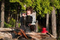 Roasting marshmallows. Boy sitting by a campfire roasting marshmallows Stock Image