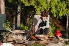 Roasting marshmallows. Boy sitting by a campfire roasting marshmallows Stock Photo