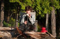 Roasting marshmallows. Boy sitting by a campfire roasting marshmallows Royalty Free Stock Photography