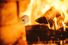 Roasting marshmallows by the fire. Cozy chalet home with fireplace Royalty Free Stock Photos