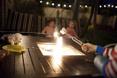 Roasting marshmallows. Over a gas fire pit Stock Photo