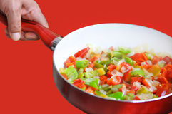 Roasting pan with vegetables. Red and green peppers and onions Isolated on red background. stock photo