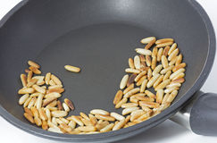 Roasting pine nuts in a frying pan Stock Images