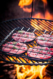 Roasting red beef with rosemary and pepper on grill Stock Photos