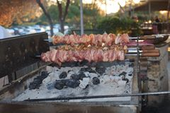 Roasting shish kebab on a brazier at an outdoor cafe Royalty Free Stock Photo