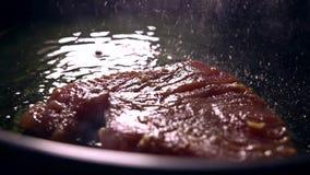 Roasting tuna fillet in sizzling oil. Slow motion close-up shot. Roasting tuna fillet in sizzling oil. Slow motion close-up video stock footage
