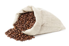 Roated coffee beans spill out of the bag Stock Images