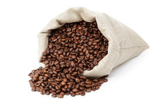 Roated coffee beans spill out of the bag royalty free stock photo